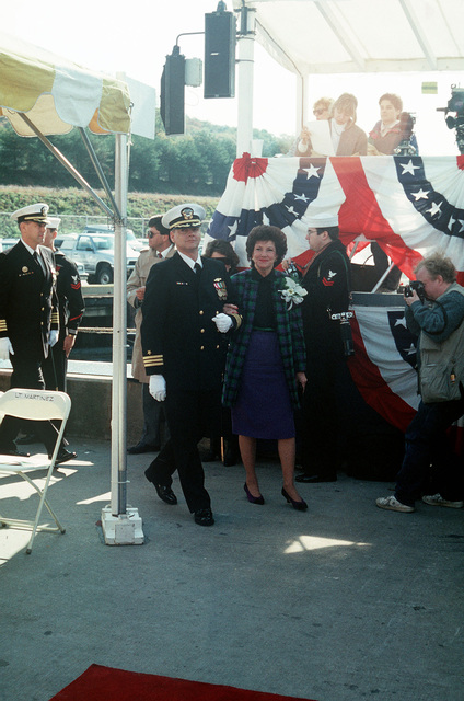 Commander Timothy M. Reichert, commanding officer of the nuclear-powered attack submarine USS TOPEKA (SSN 754), escorts Secretary of Labor Elizabeth Dole, ship's sponsor, from the speakers platform following the Topeka's commissioning ceremony