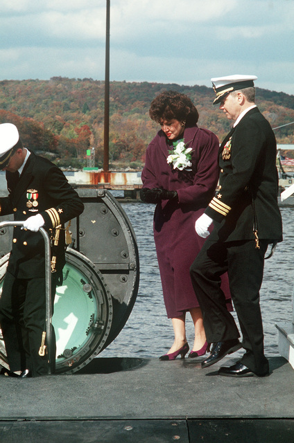 Commander Timothy M. Reichert, commanding officer of the nuclear-powered attack submarine USS TOPEKA (SSN 754), escorts Secretary of Labor Elizabeth Dole, ship's sponsor, as she prepares to tour the vessel following its commissioning ceremony