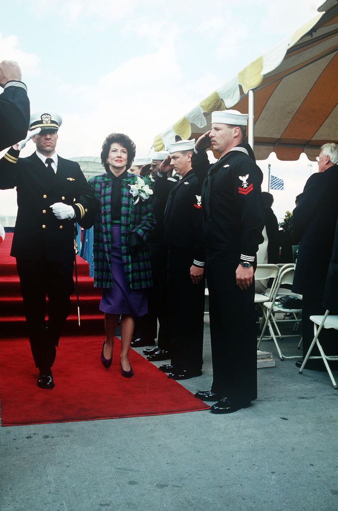 Sideboys salute as Lieutenant David P. Reber, sonar officer, escorts Secretary of Labor Elizabeth Dole, ship's sponsor, from the speakers platform on the deck of the nuclear-powered attack submarine USS TOPEKA (SSN 754) following the vessel's commissioning ceremony