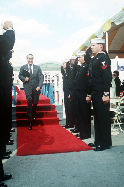 Sideboys salute as Senator Robert Dole, US Senate minority leader, departs from the speakers platform following the commissioning ceremony for the nuclear-powered attack submarine USS TOPEKA (SSN 754). Dole delivered the principal address at the event