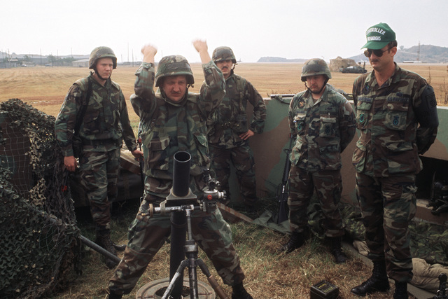 An exercise evaluator watches as members of the 8th Security Police Squadron mortar crew prepare to fire their M-29A1 81 mm mortar during the air base ground defense Exercise FOAL EAGLE '89