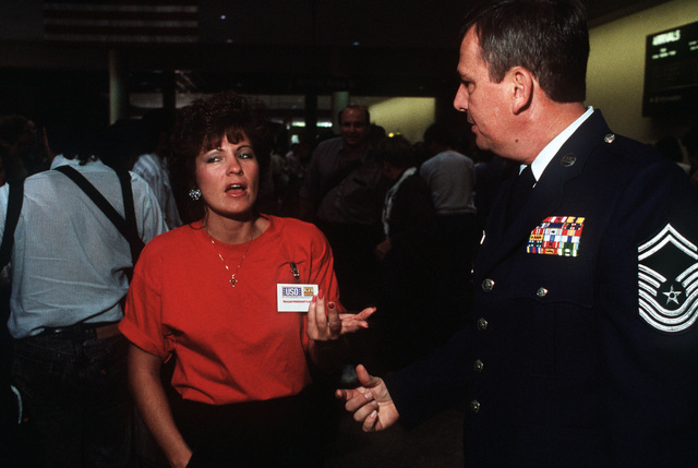 Bonnie Boring speaks with CMSGT Ellis Barton at Los Angeles International Airport following her trip to Camp Kinser, Japan. Boring was one of 230 dependents of military personnel who visited loved ones stationed in Japan and later made their return trip to the United States aboard former President Ronald Reagan's chartered Boeing 747 aircraft. Both Reagan and his wife, Nancy, accompanied the travelers