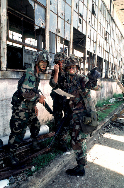 Three soldier of 2nd Platoon, Company B, Task Force 2-27, pause near an abandoned warehouse after hearing a gunshot. The platoon was conducting a patrol through the streets of the town near a Panamanian Defense Force (PDF) barracks as part of a readiness exercise