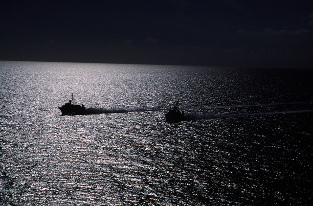 Two patrol combatant missile hydrofoils (PHMs) are silhouetted against the waters of the gulf while on patrol. The hydrofoils operate out of Key West, Florida, as part of PHM Squadron 2, which is used extensively in the nation's drug interdiction program