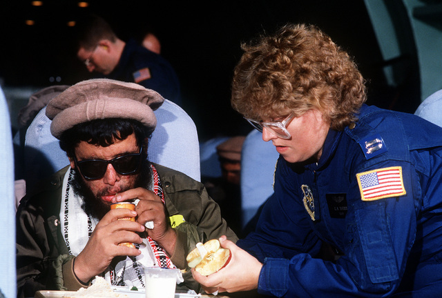 CAPT. Carol Theiss of the 2nd Aeromedical Evacuation Squadron helps a patient with his meal during a medical evacuation flight from Islamabad, Pakistan, to Rhein-Main Air Base, West Germany, aboard a 17th Military Airlift Squadron C-141B Starlifter aircraft. Twenty-four rebels wounded in Afghanistan's civil war are being evacuated to hospitals in Europe and the United States for donated medical treatment