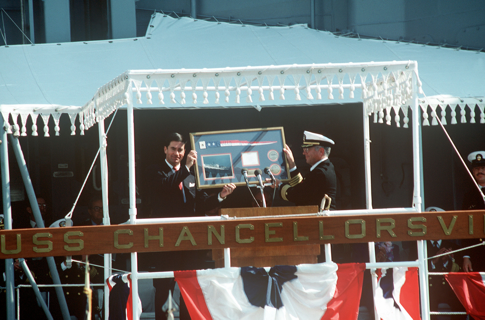 Senator Charles S. Robb, D-VA, principal speaker, and Captain Gordon H. Rheinstrom, commanding officer of the guided missile cruiser USS CHANCELLORSVILLE (CG 62), display a commemorative plaque to guests during the vessel's commissioning ceremony