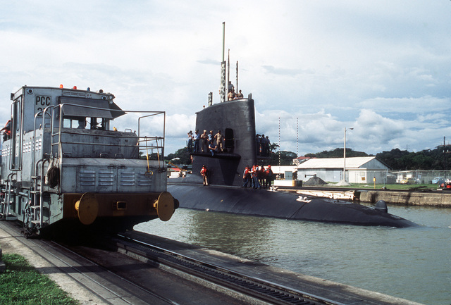 Crew members stand on the sail and diving planes of the nuclear-powered attack submarine USS SHARK (SSN-591) as locomotives pull it through the Miraflores Locks of the Panama Canal. The submarine is en route to the Pacific Ocean