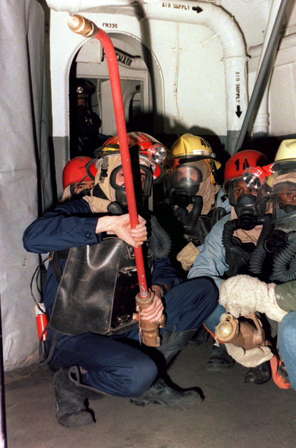 Firefighters battle a mock blaze during a damage control exercise aboard the aircraft carrier JOHN F. KENNEDY (CV 67). The men are wearing oxygen breathing apparatuses
