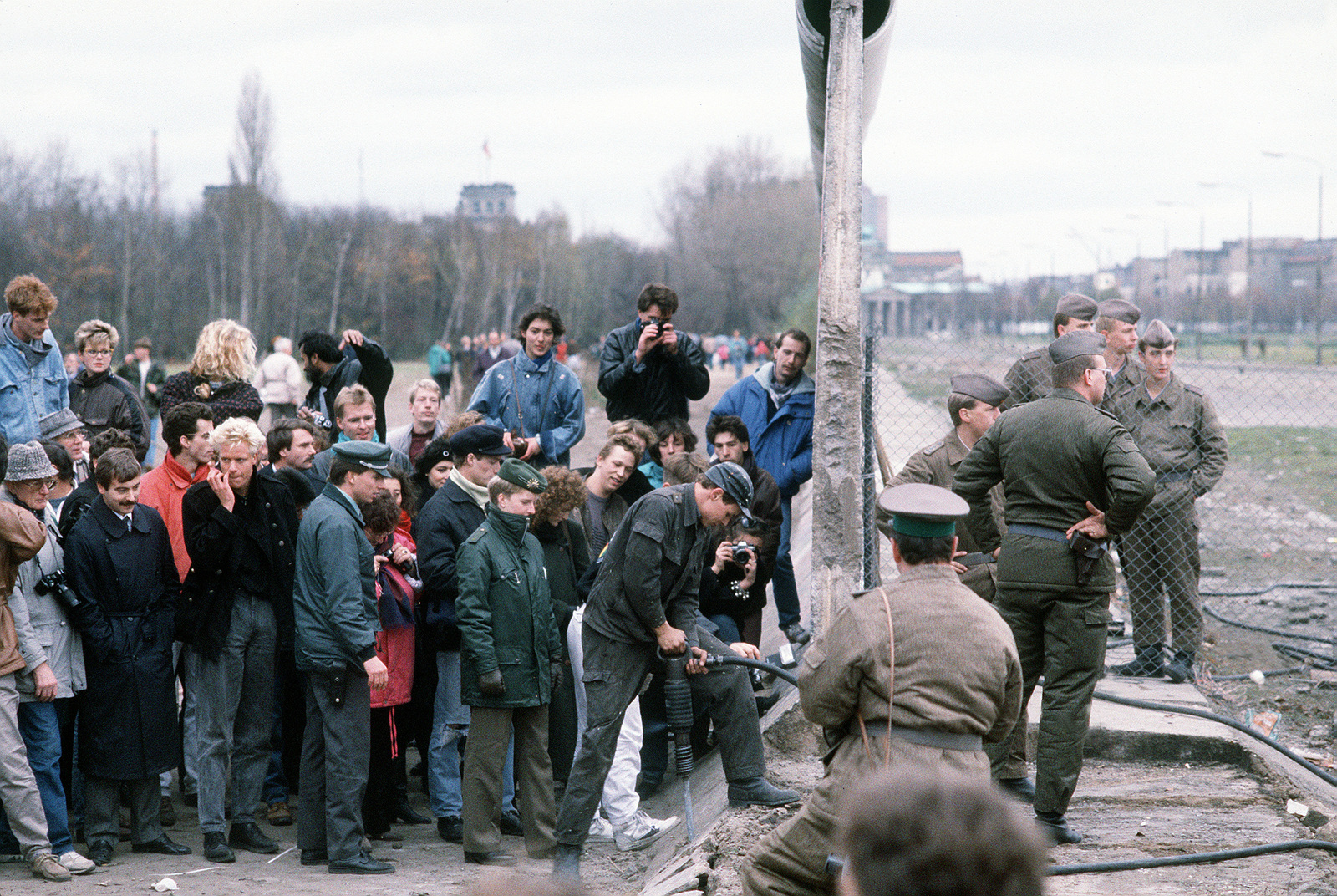 A crowd gathers on the West German side of the Berlin Wall at Potsdamer Platz to watch as the structure is dismantled