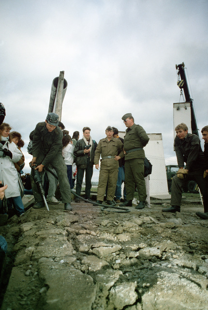 East German police and West German citizens watch as a workman dismantled a section of the Berlin Wall at Potsdamer Platz