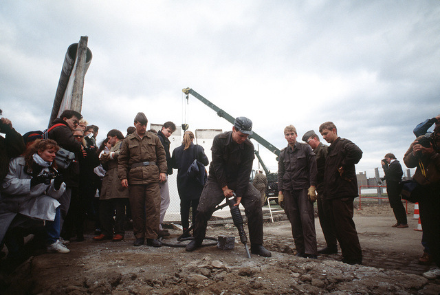 East German police and West German citizens watch as a workman dismantles a section of the Berlin Wall at Potsdamer Platz