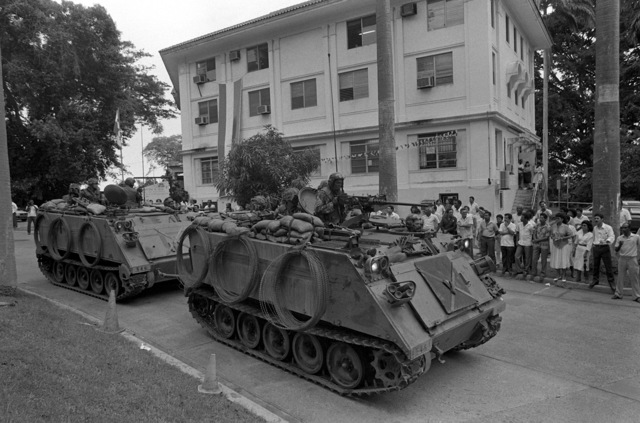 Two M113 armored personnel carriers from 4th Battalion, 6th Infantry, 5th Infantry Division (Mech.), pass a crowd of demonstrators standing in front of a Panamanian government building near the Gorgas Army Community Hospital complex. The demonstrators were protesting the decIsion to establish vehicle inspection points in response to recent bomb threats against US forces in Panama