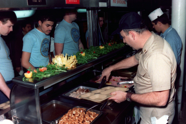 Mess Management SPECIALIST CHIEF Cohen serves Thanksgiving Day dinner to food service attendants in the galley of the aircraft carrier JOHN F. KENNEDY (CV 67)