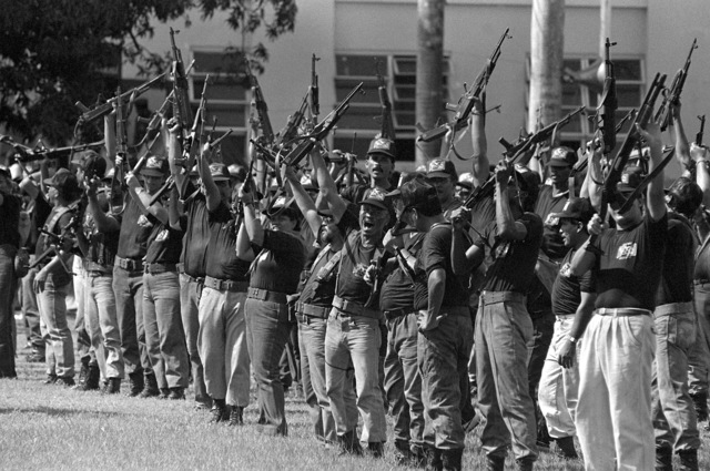 """Members of one of General Manuel Noriega's loosely organized """"Dignity Battalions"""" raise their weapons in a salute to the general during a rally aboard the joint US/Panamanian base"""
