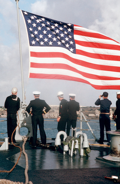 Crew members observe the coastline of Malta from the fantail of the guided missile cruiser USS BELKNAP (CG 26), flagship of the United States Sixth Fleet. The ship is in port in preparation for the summit meeting between President George H.W. Bush and Soviet Chairman Mikhail Gorbachev to be held on December 2-3