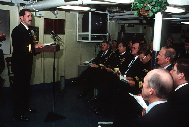 A chaplain addresses President George H. W. Bush, Sixth Fleet Commander Vice Adm. James D. Williams (on the President's right), Secretary of State James Baker and aides aboard the guided missile cruiser USS BELKNAP (CG-26). Bush is visiting the Sixth Fleet flagship prior to his summit meeting with Soviet Chairman Mikhail Gorbachev on December 2-3