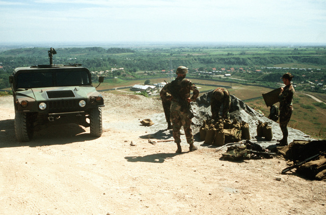 Members of the 3rd Security Police Squadron and the Army's 25th Infantry Division (Light) fill sand bags near an M1038 High-Mobility Multipurpose Wheeled Vehicle (HMMWV) as they prepare a position near a fuel depot. U.S. Army troops that were in the Philippines for an exercise have been called upon to augment base security forces as the Filipino government fights to put down a coup attempt by rebel factions within the nation's armed forces