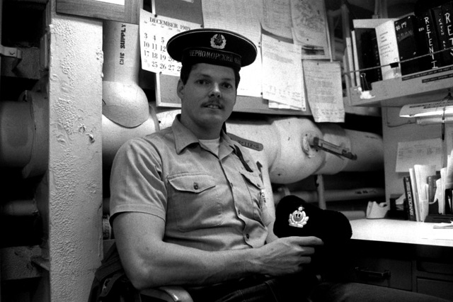 Navy Counselor 1ST Class Rick Hudson displays hats he obtained as souvenirs while visiting the Soviet guided missile cruiser SLAVA during the Malta Summit between President George H.W. Bush and Soviet President Mikhail Gorbachev. Hudson is a crew member aboard the guided missile cruiser USS BELKNAP (CG 26)