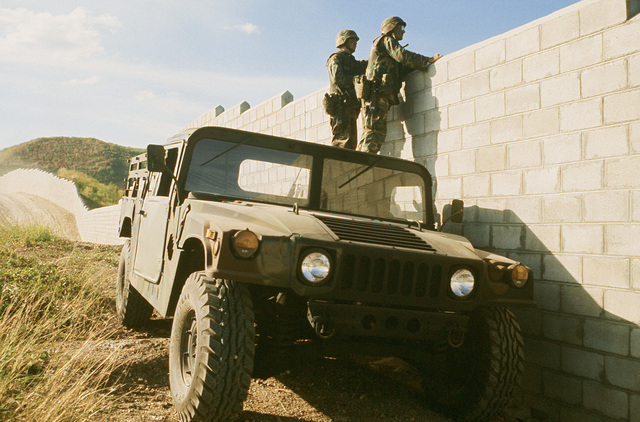PFC James Holyfield and SSG Sam Zachardia of the 25th Infantry Division (Light) stand on the roof of an M998 High-Mobility Multipurpose Wheeled Vehicle (HMMWV) to look over the perimeter wall. U.S. Army troops that were in the Philippines for an exercise have been called upon to augment base security forces as the Filipino government fights to put down a coup attempt by rebel factions within the nation's armed forces