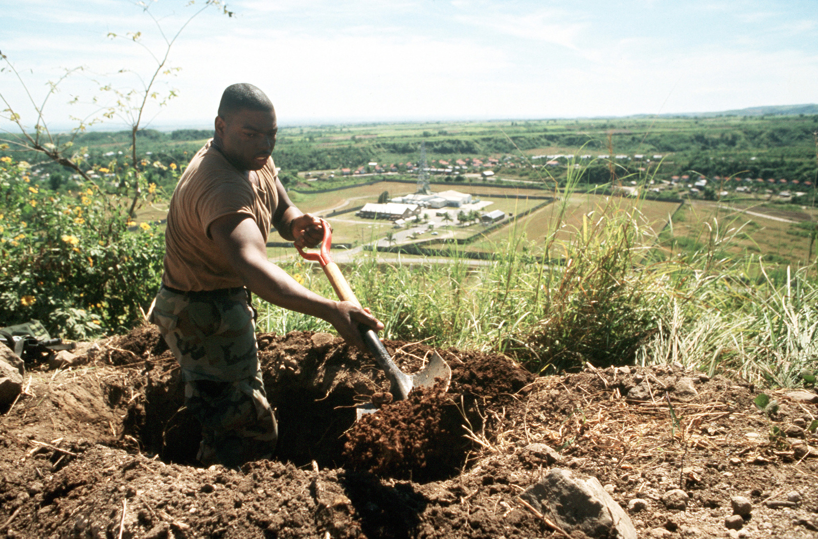 PFC Samuel Baines of the 25th Infantry Division (Light) digs a fighting hole near a fuel depot. U.S. Army troops that were in the Philippines for an exercise have been called upon to augment base security forces as the Filipino government fights to put down a coup attempt by rebel factions within the nation's armed forces
