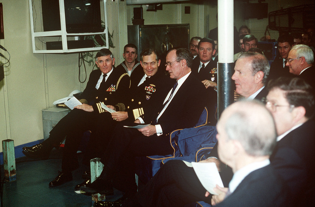 President George H.W. Bush attends a session with Sixth Fleet Commander Vice Admiral James D. Williams (on the President's right), Secretary of State James Baker and aides aboard the guided missile cruiser USS BELKNAP (CG 26). Bush is visiting the Sixth Fleet flagship prior to his December 2-3 summit meeting with Soviet Chairman Mikhail Gorbachev