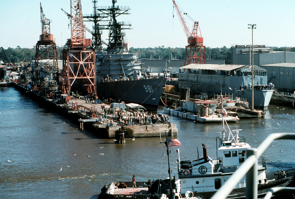 Sailors and shipyards workers watch as the battleship USS WISCONSIN (BB-64) moves away from the pier after a visit.  Tied up at center is the destroyer USS JOHN HANCOCK (DD-981)