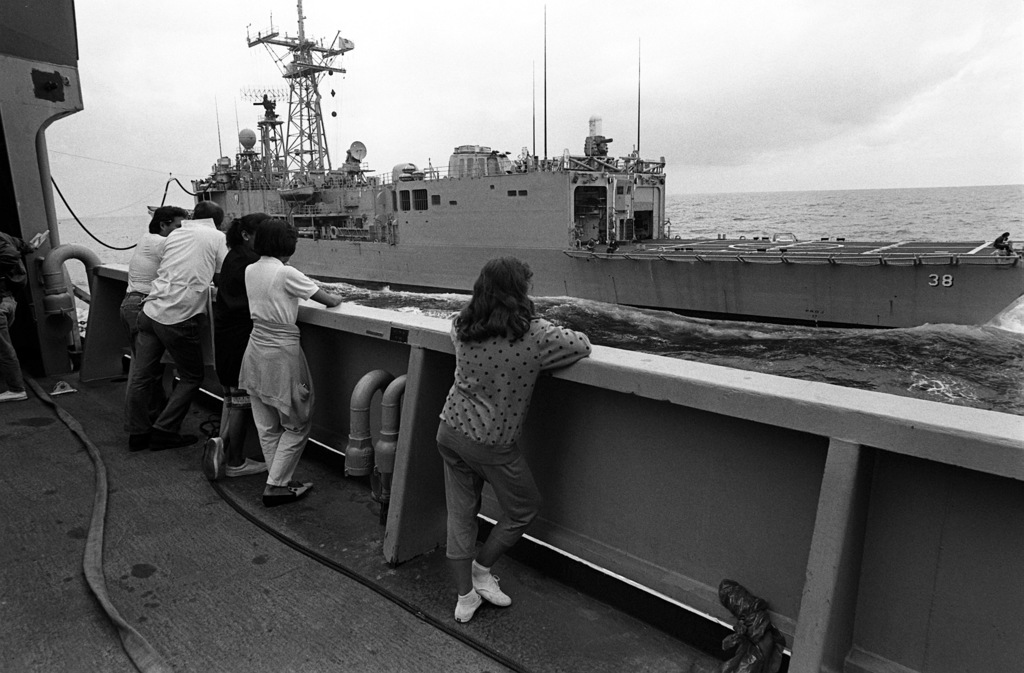Standing along the starboard side of the combat stores ship USNS SPICA (T-AFS-9), dependents watch as fuel is transferred from the SPICA to the guided missile frigate USS CURTS (FFG-38). One hundred and fifty dependents and guests spent the day on the ship, which is home-ported at U.S. Naval Station, Subic Bay, Philippines