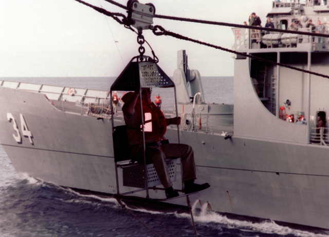 An officer in a transfer-at-sea chair on a manila highline rig travels from the aircraft carrier USS JOHN F. KENNEDY (CV 67) to the ammunition ship USS SANTA BARBARA (AE 28) during an underway replenishment