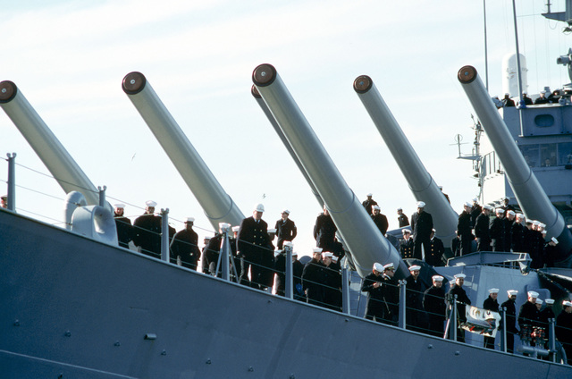 Crew members surround the Mark 7 16-inch/50 caliber guns from the No. 1 turret aboard the battleship USS IOWA (BB 61) as the vessel returns to home port following deployment