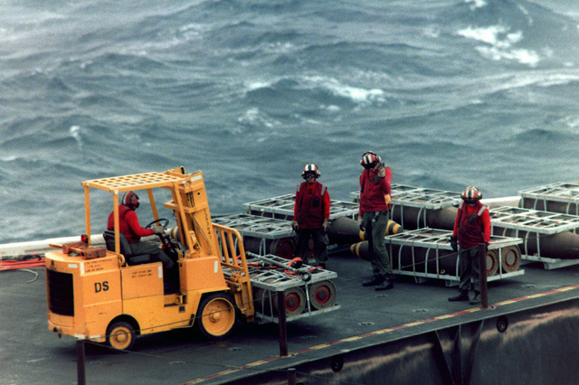 A flight deck crew member uses a forklift to move pallets of bombs aboard the aircraft carrier USS JOHN F. KENNEDY (CV 67) during a vertical replenishment operation