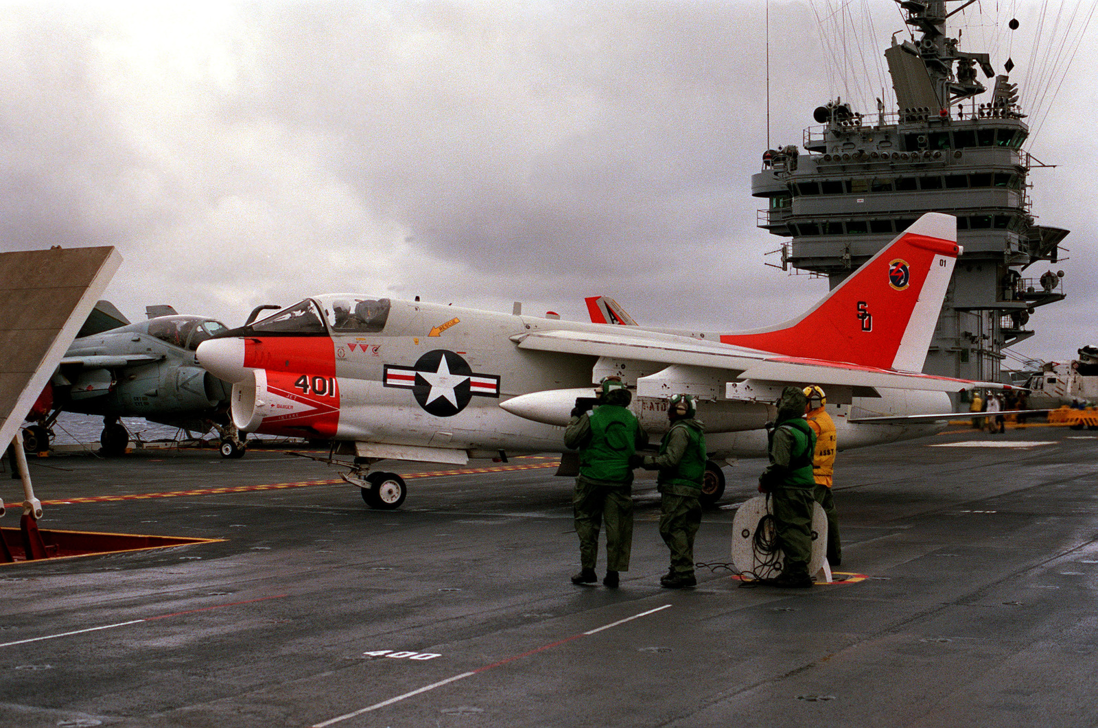 An A-7 Corsair II aircraft is positioned behind the jet blast deflector on the flight deck of the nuclear-powered aircraft carrier USS THEODORE ROOSEVELT (CVN 71)