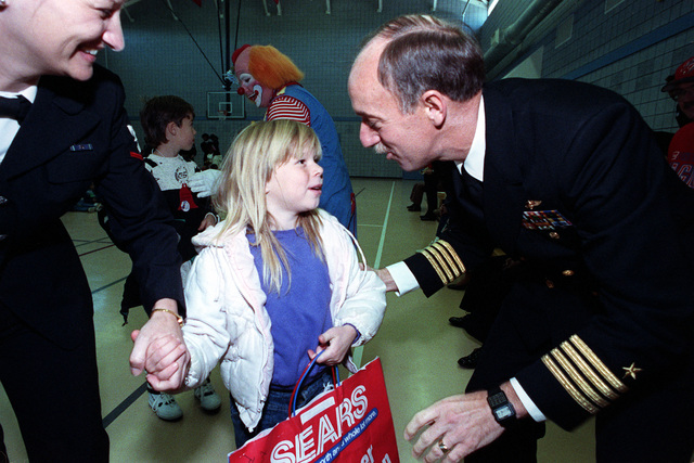 """Captain (CAPT) H.A. """"Bud"""" Jupin, Commanding Officer of the air station, talks to a child after giving her a bag of gifts during the air station's Civilian Welfare and Recreation Association Christmas party"""