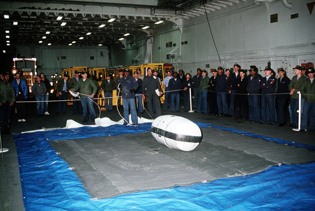 Crew members watch as their companions prepare to open an inflatable lifeboat during a demonstration of the craft aboard the amphibious assault ship USS WASP (LHD-1)