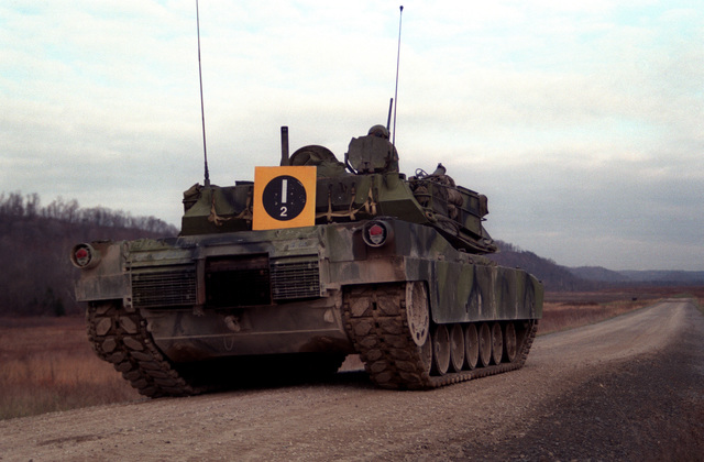 A right rear view of a US Army M1 M-1 Abrams main battle tank on a road near one of the fort's firing ranges. The tank will be test firing 105 mm ammunition developed by the Army with the assistance of Naval Ordnance Station, Louisville, Kentucky