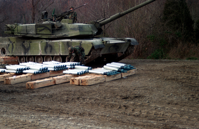 Rows of 105 mm tank ammunition lie beside one of two US Army M-1 Abrams main battle tanks that are test firing ammunition developed by the Army with the assistance of Naval Ordnance Station, Louisville, Kentucky. In the front row are M-490 target practice tracer (TP-T rounds; the four rows to the left contain M-724A1 discarding-sabot target practice tracer (TPDS-T) rounds