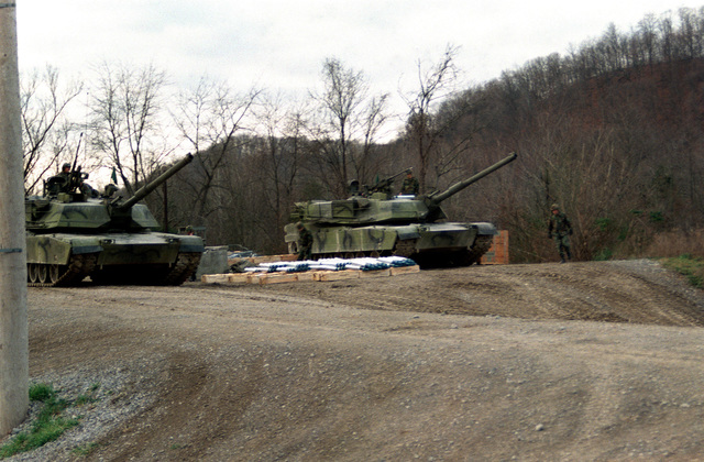 Two US Army M1 M-1 Abrams main battle tanks wait on the firing line. The tanks will be test firing 105 mm ammunition developed by the Army with the assistance of Naval Ordnance Station, Louisville, Kentucky. The ammunition to be tested is stacked on packing cases between the tanks