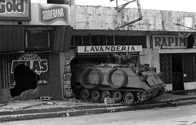 A U.S. Army M-113 armored personnel carrier guards a street near the destroyed Panamanian Defense Force headquarters building during the second day of Operation Just Cause