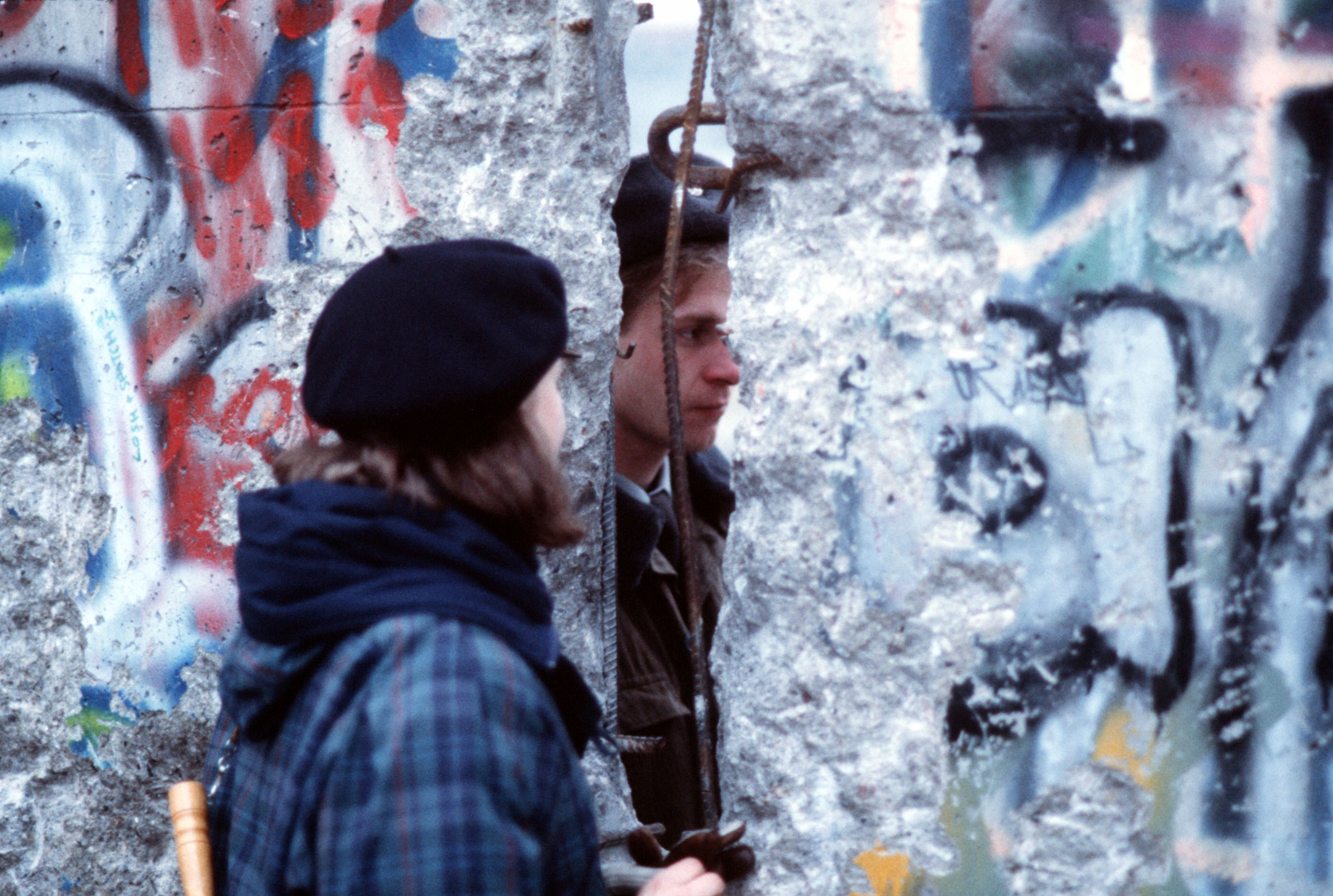 A West German girl speaks with an East German guard through an opening in the Berlin Wall