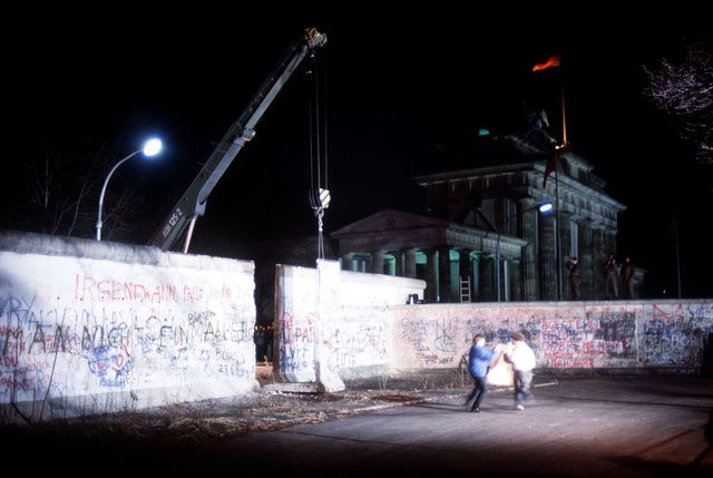 Local residents rejoice as a crane removes a section of the Berlin Wall beside the Brandenburg Gate