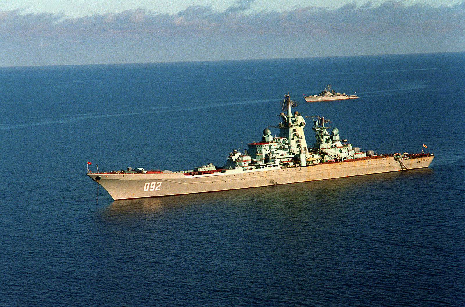 A port view of the Soviet nuclear-powered guided missile cruiser KIROV at anchor. In the background is a Soviet Krivak I-class guided missile frigate