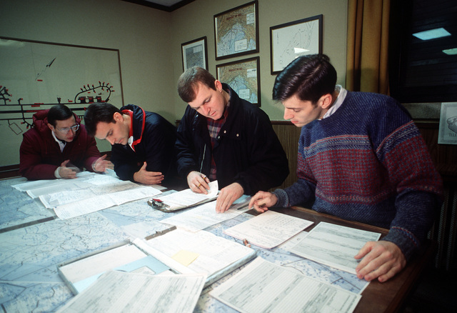 Members of a 37th Tactical Airlift Squadron flight crew prepare new flight plans after diverting their flight to Aviano because of heavy snow and low visibility at their original destination of Bucharest, Romania. Their aircraft is loaded with medical supplies provided by the U.S. Army's 7th Medical Command as part of a relief effort for the citizens of revolt-torn Romania. The crew is in civilian clothes on this mission for diplomatic reasons