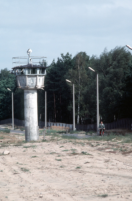 A cyclist passes an abandoned watchtower at the former Checkpoint Bravo following Germany's reunification