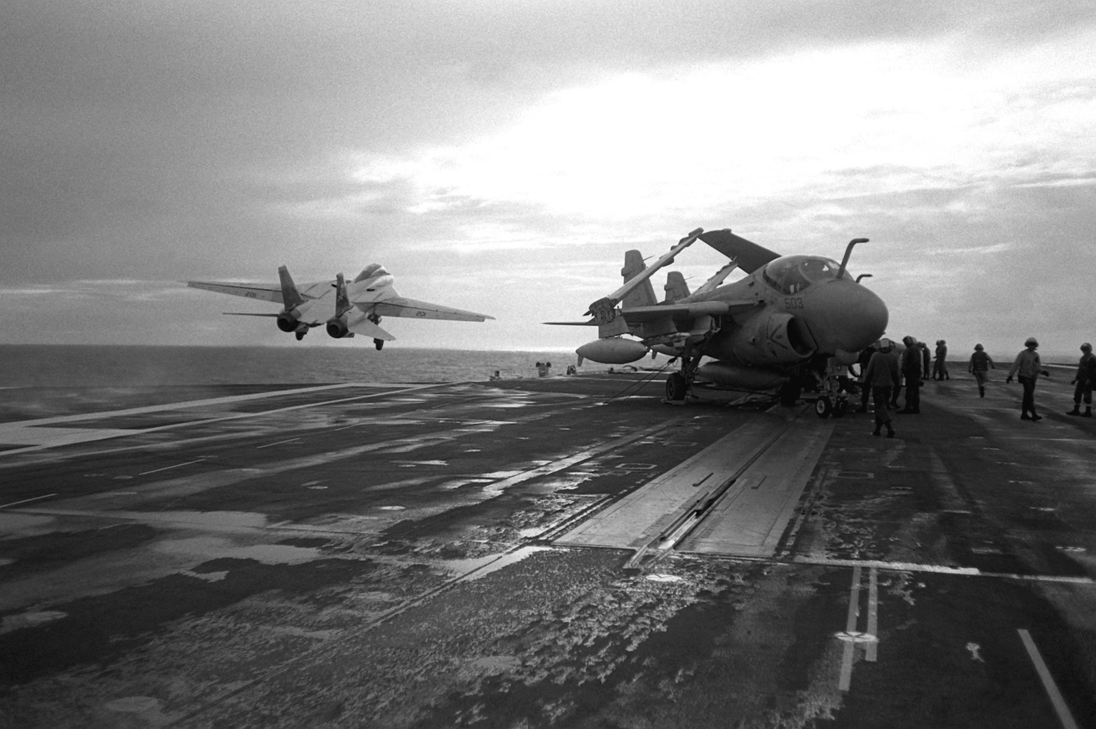 A Fighter Squadron 84 (VF-84) F-14A Tomcat aircraft, left, is launched from one of the waist catapults aboard the nuclear-powered aircraft carrier USS ABRAHAM LINCOLN (CVN-72). An attack squadron 65 (VA-65) A-6E Intruder aircraft is at right