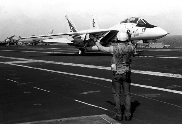 A flight deck crew member signals to the pilot of a Fighter Squadron 14 (VF-14) F-14A Tomcat aircraft readied for launch from the aircraft carrier USS JOHN F. KENNEDY (CV 67) during FLEET EX 1-90