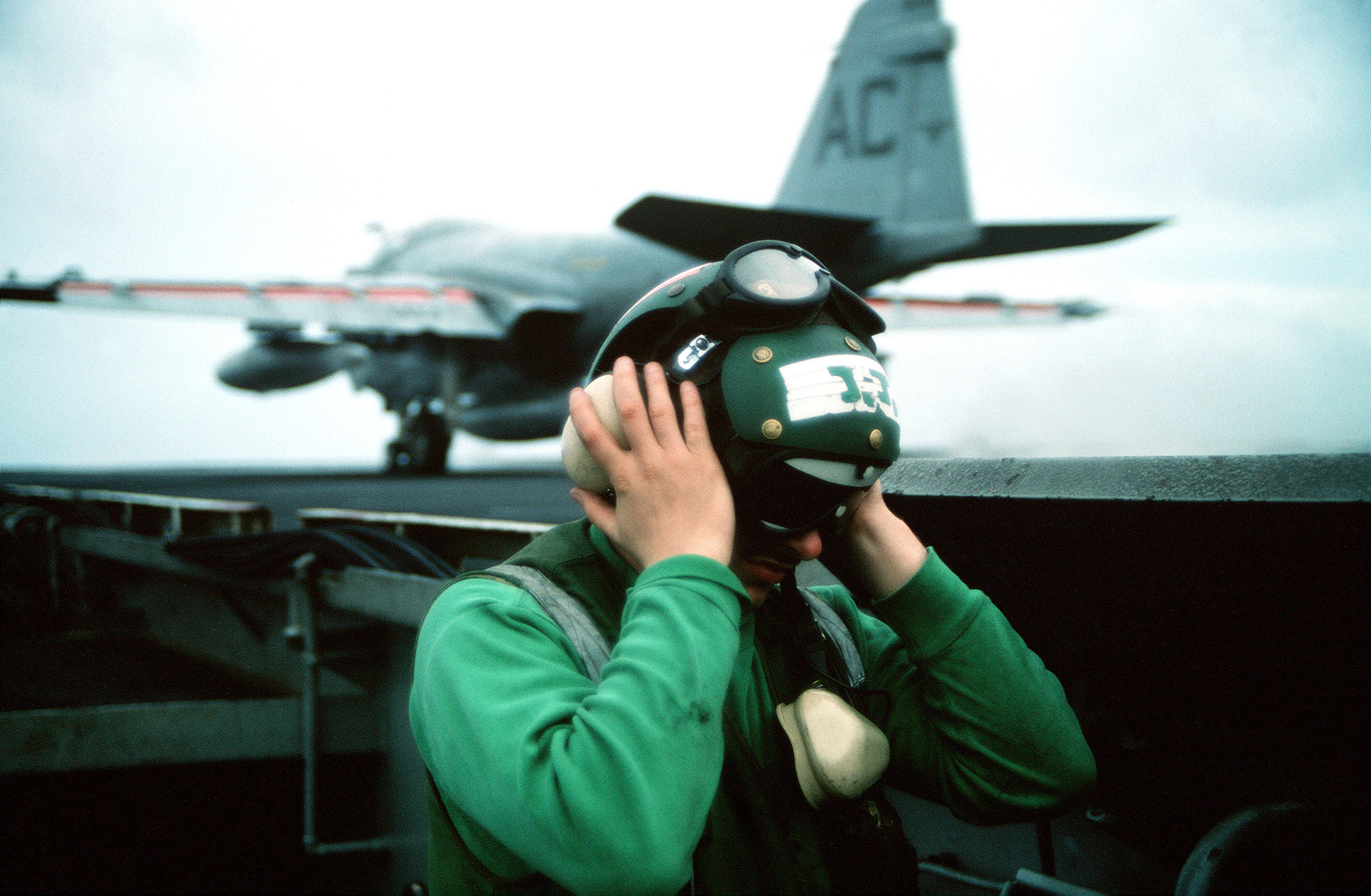 A flight deck crewman adjusts his hearing protectors while standing on a catwalk aboard the aircraft carrier USS JOHN F. KENNEDY (CV-67) during Fleet Ex 1-90. An Attack Squadron 75 (VA-75) A-6E Intruder aircraft is in the background