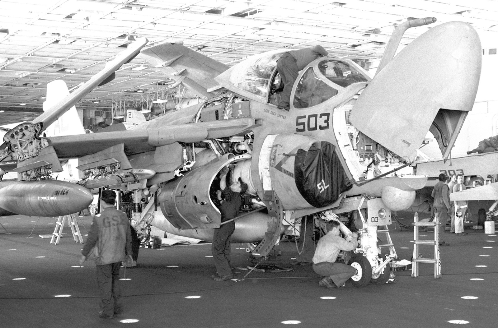 A gas turbine systems technician E (electrical) approaches a partially disassembled A-6E Intruder aircraft being worked on in the hangar bay of the aircraft carrier USS JOHN F. KENNEDY (CV-67) during FLEET EX 1-90