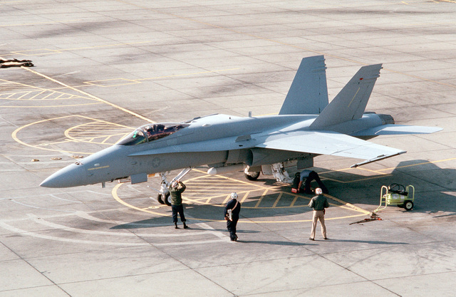 A ground crewman signals to the pilot of the first F/A-18C(N) Hornet aircraft to be delivered to Strike Fighter Squadron 147 (VFA-147) as another crewman chocks the aircraft's wheels following its arival at the air station from McDonnell-Douglas corporate facilities in St. Louis. The squadron is making the transition from A-7E Corsair II aircraft to the more technologicaly advanced Hornet