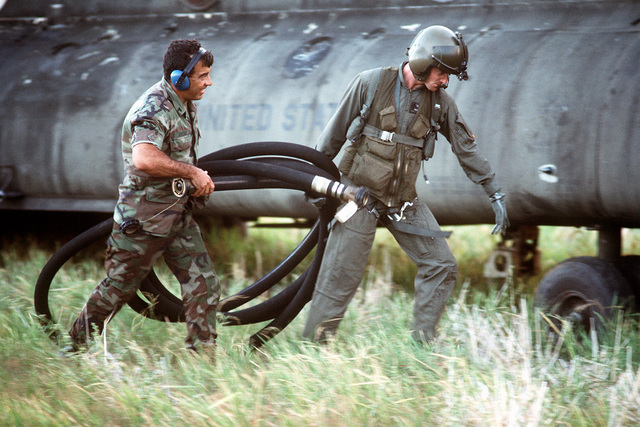 A helicopter crewman helps a soldier carry a fuel hose into a field beside a CH-47 Chinook helicopter during Operation Just Cause. Both soldiers are from 1ST Battalion, 228th Aviation Regiment