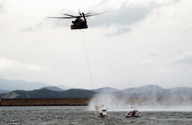 A Helicopter Mine Countermeasures Squadron 15 (HM-15) KH-53E Sea Dragon helicopter tows a Mark 105 hydrofoil sled as a rigid hull inflatable boat (RIB) maintains its position beside the sled during a minesweeping exercise, part of the joint US/South Korean Exercise VALIANT BLITZ'90