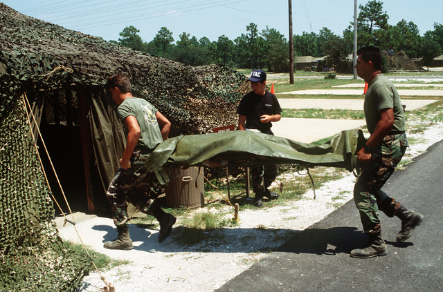 A judge from Headquarters, Tactical Air Command, records their time as team members bear a simulated battlefield casualty into the remains processing shelter during the civil engineering/services competition Readiness Challenge '90